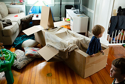 Kids engage in pretend play indoors with spacecraft made of cardboard - p1166m2106109 by Cavan Images