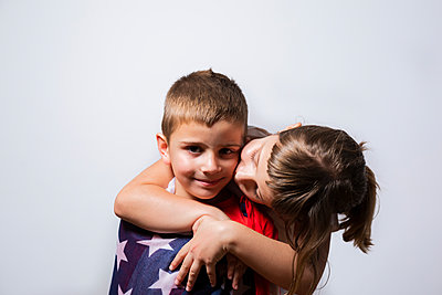6-year-old girl wrapping the U.S. flag around her 4-year-old brother - p1166m2193953 by Cavan Images