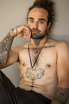 Young man with bare chest and lots of tattoos - p1640m2245804 by Holly & John