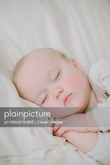 Closeup of sleeping baby girl's face in white bed - p1166m2191805 by Cavan Images