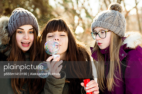 Caucasian girls blowing bubbles outdoors in winter - p555m1413190 by Aleksander Rubtsov