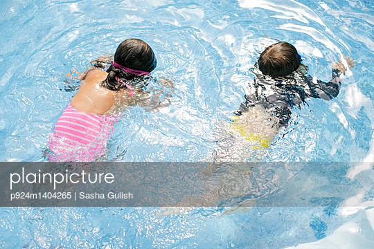 Overhead view of boy and girl swimming in outdoor swimming pool
