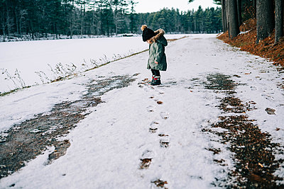 Little girl staring at her feet amidst the snow. - p1166m2157330 by Cavan Images