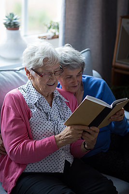 Senior friends reading a book together at home - p1315m1566266 by Wavebreak