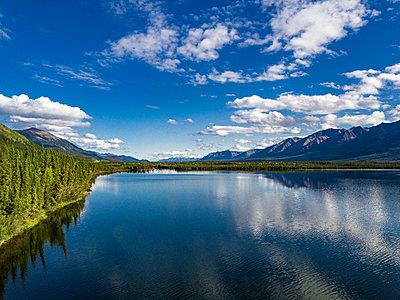 Wolken spiegeln sich in einem Bergsee - p1455m2203782 von Ingmar Wein