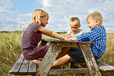 Three children playing on a small wooden table in a meadow - p1540m2200520 by Marie Tercafs