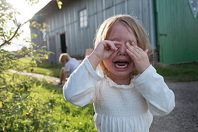 Portrait of screaming little girl covering eyes with her hands - p300m2042430 by Katharina Mikhrin