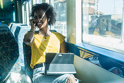 Happy young woman with earphones and tablet on a train - p300m2155855 by Uwe Umstätter