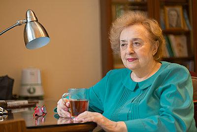 Senior woman drinking tea at desk in home office - p301m2272014 by Vladimir Godnik