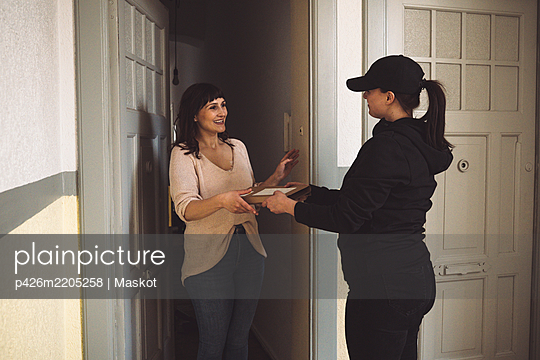 Delivery woman delivering package to smiling customer at doorstep - p426m2205258 by Maskot