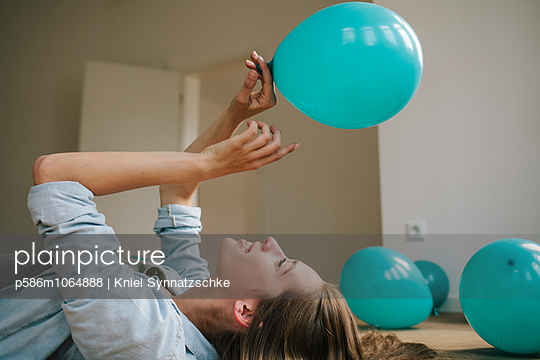 Young woman in new apartment playing with balloons - p586m1064888 by Kniel Synnatzschke
