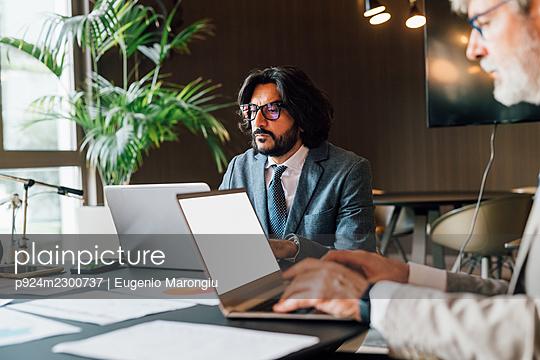 Italy, Businessmen using laptops in creative studio - p924m2300737 by Eugenio Marongiu
