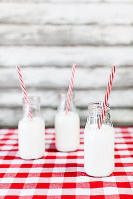 Milk bottles with striped straws on tablecloth - p1094m1015327 by Patrick Strattner