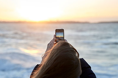 Woman takes a photo of sunset over the sea - p1124m1564790 by Willing-Holtz