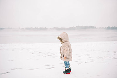Little girl standing in the rain on an icy beach. - p1166m2157462 by Cavan Images