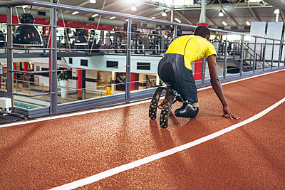 Disabled African American male athletic in starting position on running track in fitness center - p1315m2130235 by Wavebreak