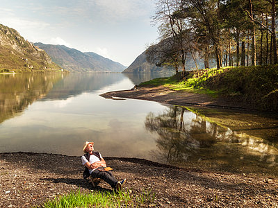 Italy, Lombardy, senior man relaxing at Lake Idro - p300m2103392 by Albrecht Weißer
