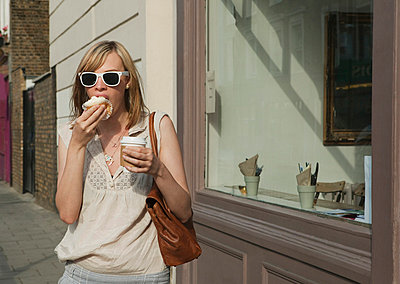 Woman eating in street - p4296627f by Clarissa Leahy
