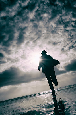 Rearview man in hat and coat running on beach with stormy sky - p597m2230602 by Tim Robinson