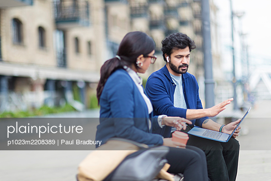 Business people with laptop working on outdoor bench - p1023m2208389 by Paul Bradbury