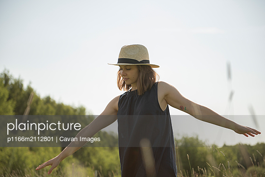 Woman walking in a field with her arms like a plane against blue sky - p1166m2112801 by Cavan Images