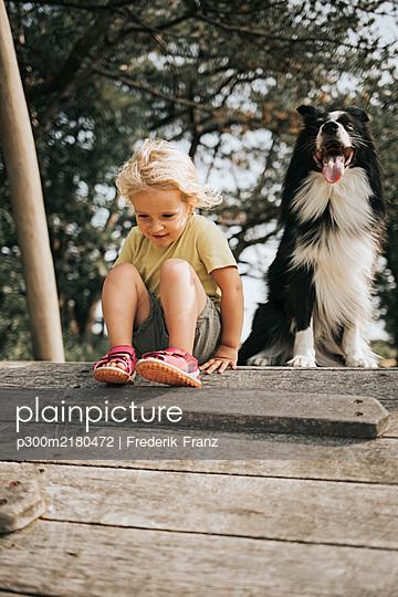 Netherlands, Schiermonnikoog, girl with Border Collie sitting on boardwalk in the forest - p300m2180472 by Frederik Franz