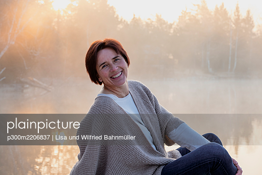 Portrait of adult woman posing on lakeshore at foggy sunrise - p300m2206837 by Lisa und Wilfried Bahnmüller