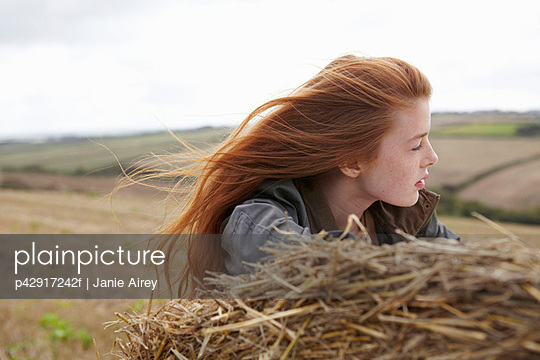 Teenage girl resting on haybale - p42917242f by Janie Airey