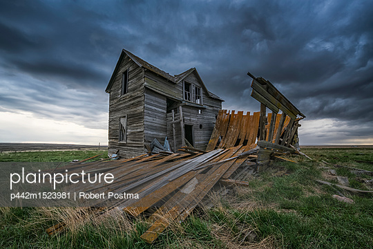 Abandoned house on the prairies with storm clouds overhead at sunset; Val Marie, Saskatchewan, Canada  - p442m1523981 by Robert Postma