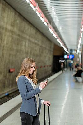 Frau liest Kurzmitteilung in der U-Bahn - p081m1124905 von Alexander Keller