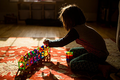 A child sits on the floor in golden morning light building with tiles - p1166m2130173 by Cavan Images