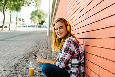Woman listening music on smart phone through headphone while sitting against brick wall - p300m2226713 by Xavier Lorenzo