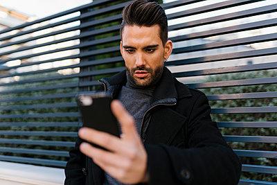 Handsome man using smart phone against metal fence - p300m2251740 by Ezequiel Giménez