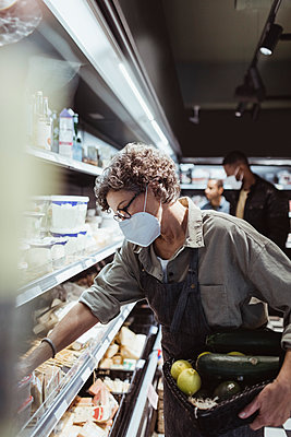 Female owner arranging food product on rack in delicatessen shop during pandemic - p426m2270696 by Maskot