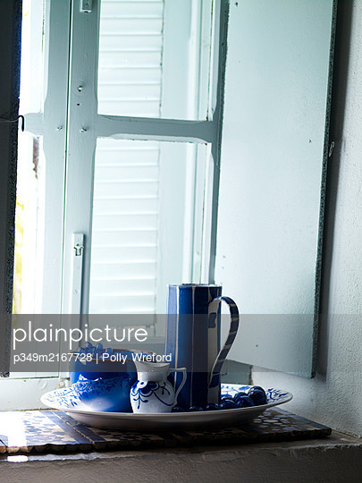 Blue and white chinaware on windowsill with light blue shutters, Spain - p349m2167728 by Polly Wreford