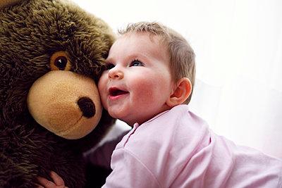 Baby kuschelt mit großem Teddy - p1196m1201698 von Biederbick & Rumpf
