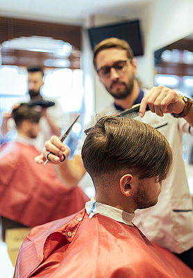 Barber cutting hair of a customer with twin brother in background - p300m1081519f by Marco Govel
