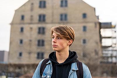 Denmark, Copenhagen, young man in front of a building looking around - p300m2102155 von VITTA GALLERY