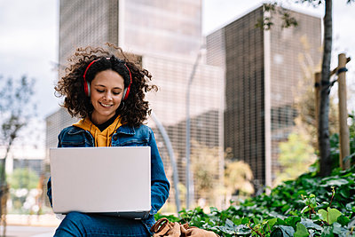 Smiling woman with wireless headphones working on laptop in city - p300m2282044 by COROIMAGE