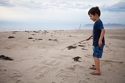 A young boy writes his name in the sand with a stick he found on the beach. - p343m1168011 by Christopher Kimmel