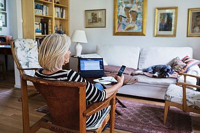 Senior woman using smart phone at home while dog relaxing on sofa - p426m1114755f by Maskot