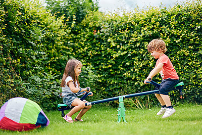 Girl and boy on toy seesaw in garden - p429m2145812 by GS Visuals