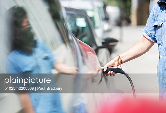 Woman charging electric car - p1023m2208369 by Paul Bradbury