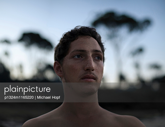 Melancholischer junger Mann in der Dämmerung - p1324m1165220 von michaelhopf