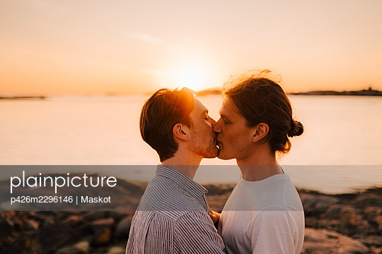 Male friends lip kissing at lakeshore during vacation - p426m2296146 by Maskot