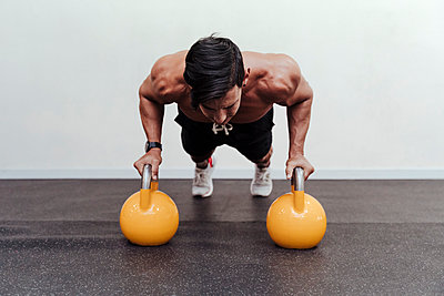 Male athlete doing push-ups on yellow kettlebell in gym - p300m2274480 by Eva Blanco
