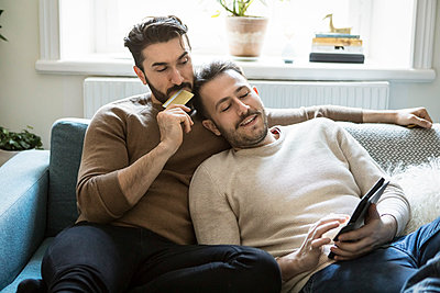 be3341b26f High angle view of homosexual couple doing online shopping while relaxing on  sofa at home -