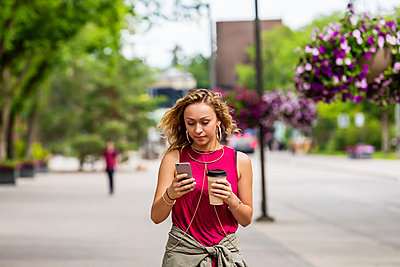 A young woman walking down a street near a university campus texting on her smart phone; Edmonton, Alberta, Canada - p442m2004180 by LJM Photo
