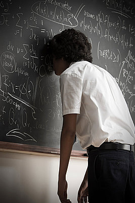 Boy leaning on blackboard - p9246016f by Image Source
