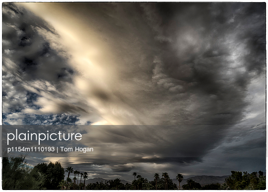 Storm clouds over oasis - p1154m1110193 by Tom Hogan